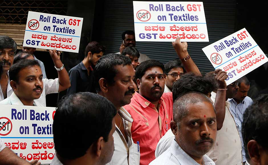 While the measure is being billed as making doing business easier by simplifying the tax structure and ensuring greater compliance, businesses, particularly small traders, are nervous about the new tax filing system. Indian textile traders hold placards as they walk past closed shops during a protest against the implementation of the nationwide GST in Bangalore. AP