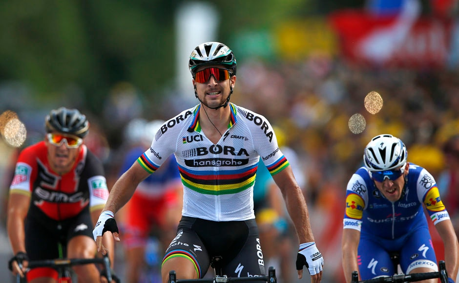 Peter Sagan of Slovakia, center, crosses the finish line ahead of Ireland's Daniel Martin, right, and Belgium's Greg van Avermaet, left, to win the third stage of the Tour de France cycling race. AP