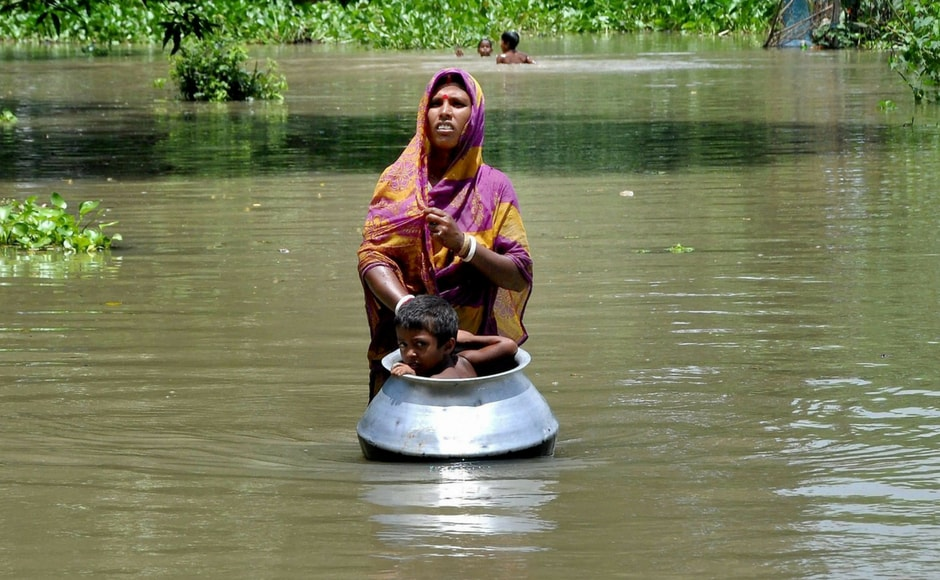 A woman with her child moves to a safer place in flood-hit Khanamukh village in Morigaon of Assam. PTI