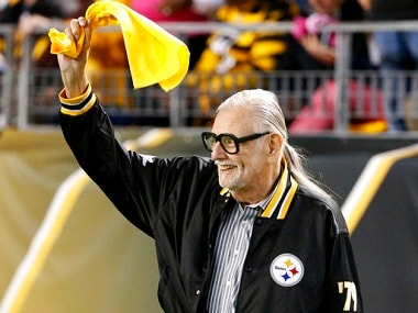 """FILE - In this Oct. 1, 2015, file photo, horror film director George Romero, who directed """"The Night of The Living Dead"""" waves a Terrible Towel before an NFL football game between the Pittsburgh Steelers and the Baltimore Ravens in Pittsburgh. It was the anniversary of the film that was made in the Pittsburgh area. Romero, whose classic """"Night of the Living Dead"""" and other horror films turned zombie movies into social commentaries and who saw his flesh-devouring undead spawn countless imitators, remakes and homages, has died. He was 77. Romero died Sunday, July 16, 2017, following a battle with lung cancer, said his family in a statement provided by his manager Chris Roe. (AP Photo/Gene J. Puskar, File)"""
