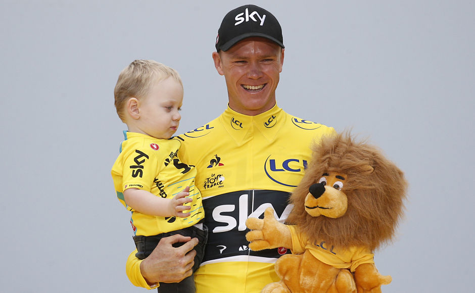 Froome holds his son Kellan on the podium after the twenty-first and last stage of the Tour de France. AP