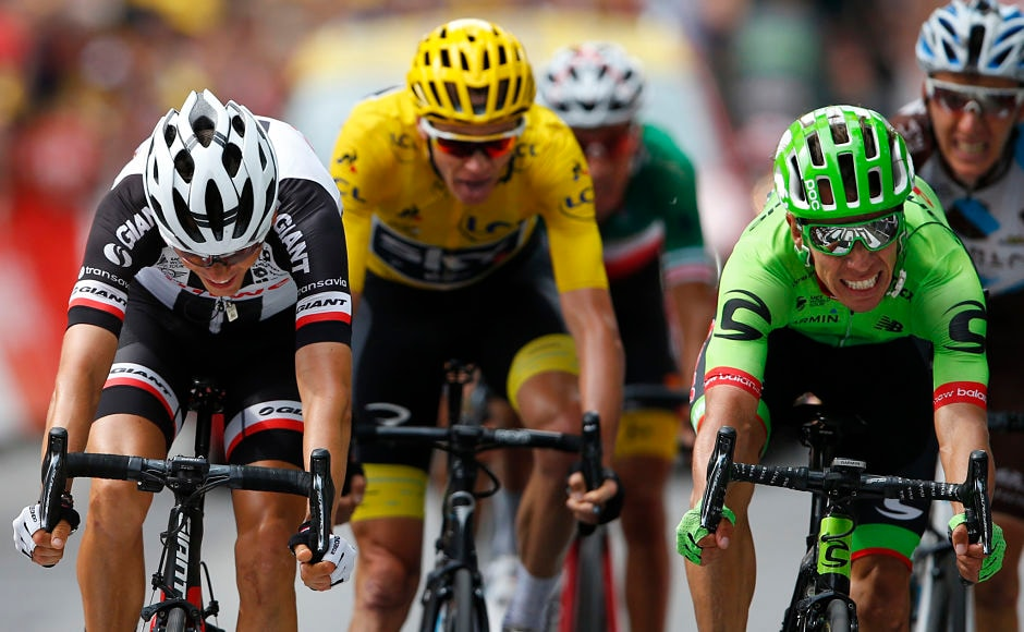 Colombia's Rigoberto Uran(R) crosses the finish line ahead of ahead of France's Warren Barguil(L), Britain's Chris Froome, wearing the overall leader's yellow jersey to win the ninth stage of the Tour de France cycling race. AP