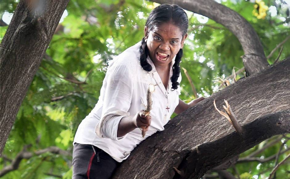 A woman climbed on top of a tree near Bombay High Court on Tuesday. PTI