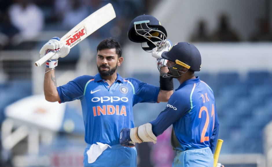 Indian Virat Kohli (L) celebrates his century with teammate Dinesh Karthik (R) during the 5th ODI of the series against the Windies at Sabina Park in Kingston, Jamaica. AFP