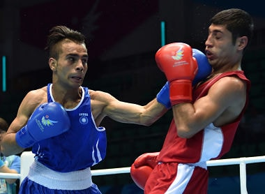 Gaurav Bidhuri of India (L) competes against Zoirov Shakhobidin of Uzbekistan during their men's quarter-final 52kg boxing match at the 17th Asian Games in Incheon on September 29, 2014. AFP PHOTO / Bay ISMOYO / AFP PHOTO / BAY ISMOYO
