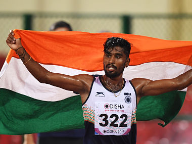 Indian athlete G Lakshmanan celebrates after winning the Gold medal in the men's 5000m runs during the first day of the 22nd Asian Athletics Championships at Kalinga Stadium in Bhubaneswar on July 6, 2017. / AFP PHOTO / Dibyangshu SARKAR