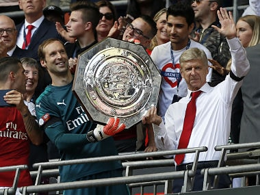 Arsenal's manager Arsene Wenger and goalkeeper Petr Cech hold up the Community Shield trophy. AFP