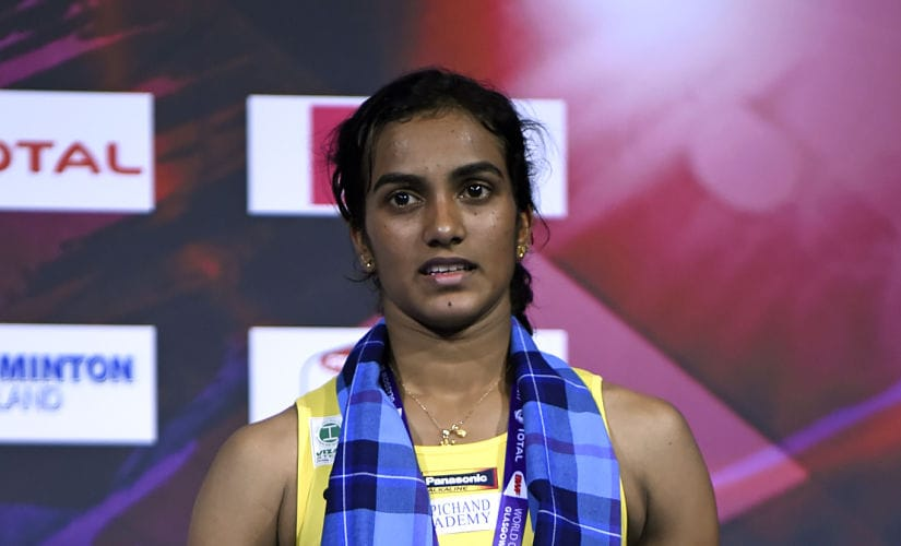 India's Sindhu Pusarla poses with her silver medal on the podium after her defeat to Japan's Nozomi Okuhara in their women's singles final match during the 2017 BWF World Championships of badminton at Emirates Arena in Glasgow on August 27, 2017. / AFP PHOTO / ANDY BUCHANAN