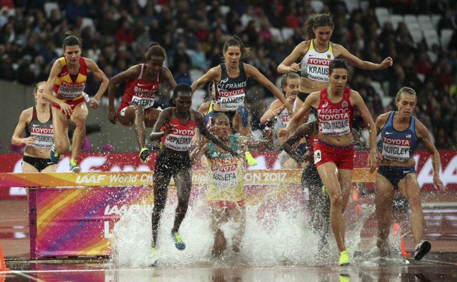 Athletes clear the water jump in a women's 3000-metre steeplechase first round heat during the IAAF World Championships in London. AP