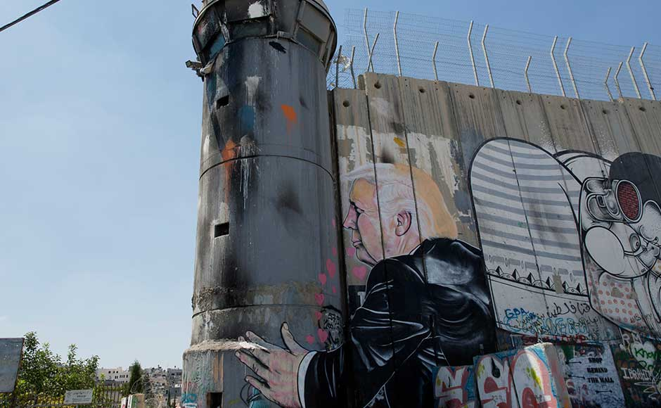 In one scene, Trump is shown hugging and kissing a real Israeli army watchtower built into the wall, as his left arm reaches around the tower. Little pink hearts flutter from Trump's mouth. AP