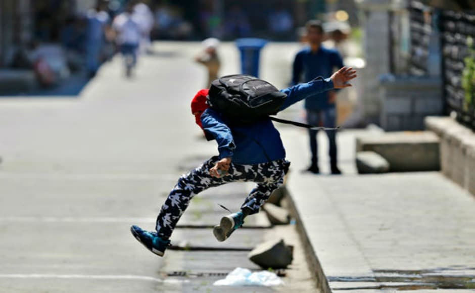 A masked Kashmiri protester jumps in the air to avoid glass marbles and stones thrown by the army on him during the protest. AP