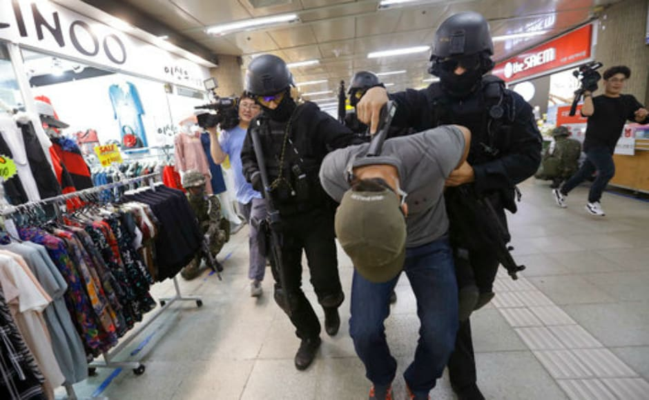 A mock terrorist is arrested by South Korean police officers during the anti-terror drill. The US and South Korea have begun the annual anti-terror drills involving almost 70,000 troops near the border that Seoul shares with North Korea. AP