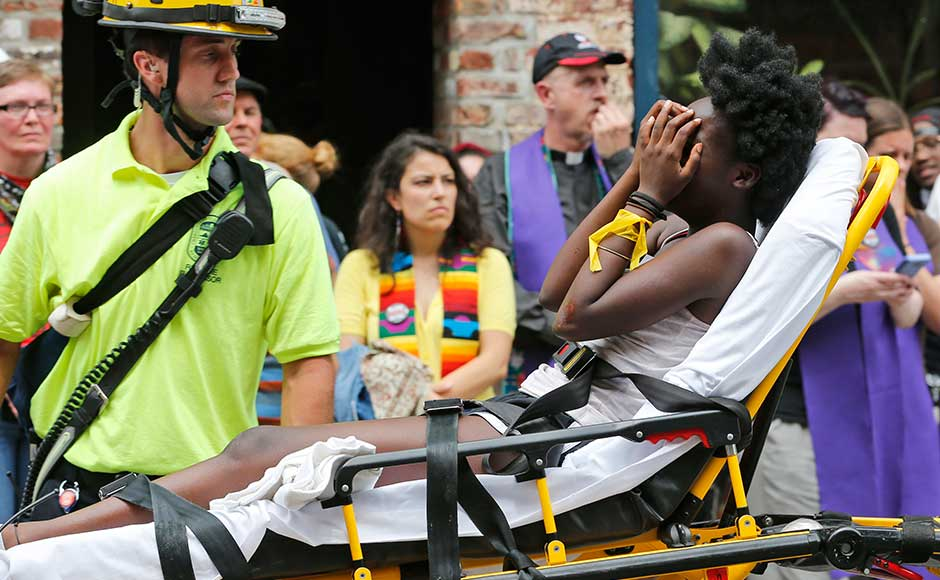 """The """"on many sides"""" ending of his statement drew the ire of his critics, who said he failed to specifically denounce white supremacy and equated those who came to protest racism with the white supremacists. Rescue personnel help an injured woman after a car ran into a large group of protesters during a white nationalist rally in Charlottesville. AP"""