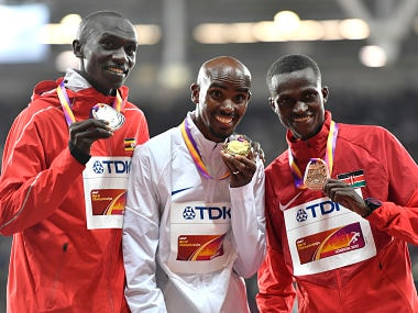Gold medalist Britain's Mohamed Farah, centre, stands with silver medalist Uganda's Joshua Kiprui Cheptegei and bronze medalist Kenya's Paul Kipngetich Tanui. AP