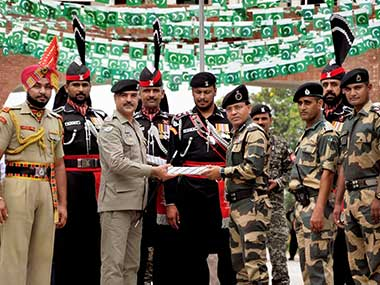 Pakistani Wing Commander Bilal (L) presents sweets to Border Security Force (BSF) Commandant Sudeep on the occasion of Pakistan's Independence Day, at the India-Pakistan Attari-Wagah border post on Monday. PTI