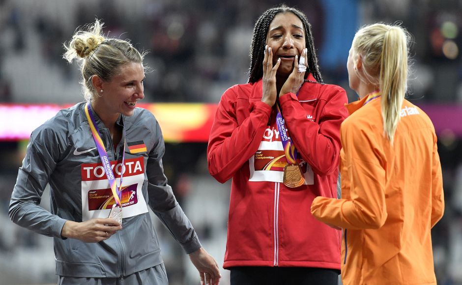 Belgium's Nafissatou Thiam, centre, celebrates on the podium after receiving her gold medal for the heptathlon with silver medalist Germany's Carolin Schaefer, left, and bronze medalist Netherlands' Anouk Vetter, right, at the World Athletics Championships in London on Sunday. AP