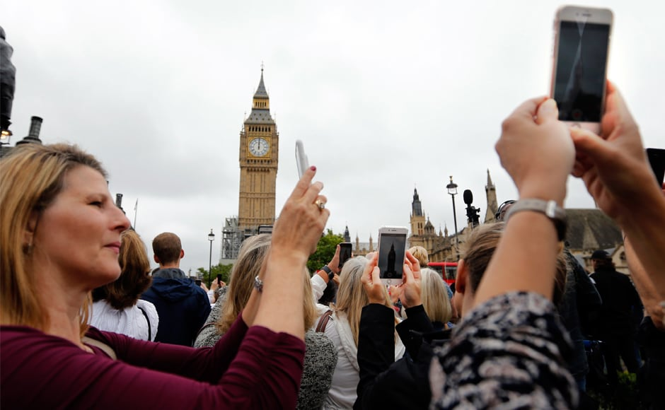 People record the last bell bong at the Elizabeth Tower in London. The Great Bell, the official name for Big Ben, traditionally rings every hour to the note of E, accompanied by four quarter bells that chime every 15 minutes. AP