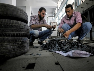 Engineering students, Mostafa Saeed Ali and Mohamed Amr cut up car tires in Cairo. Reuters.