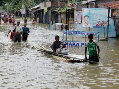 File image of people wading through a flooded road in South Dinajpur in West Bengal. PTI