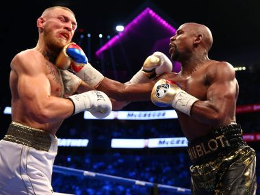 Floyd Mayweather lands a hit against Conor McGregor during their boxing match. Reuters