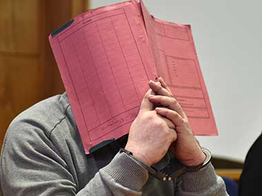 Niels Hoegel, accused of multiple murder and attempted murder of patients, covering his face with a file at the district court in Oldenburg, Germany. AP