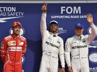Mercedes driver Lewis Hamilton of Britain, center, stands on the podium with Mercedes driver Valtteri Bottas of Finland, right, and Ferrari driver Sebastian Vettel of Germany, left, after the qualifying session ahead of the Belgian Formula One Grand Prix in Spa-Francorchamps, Belgium, Saturday, Aug. 26, 2017. Lewis Hamilton has secured pole position for the Belgian Grand Prix, equalling Michael Schumacher's record of 68 career poles. (AP Photo/Geert Vanden Wijngaert)