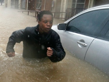 A young man fights the current from the overflow of Buffalo Bayou as he makes his way through floodwaters. AP