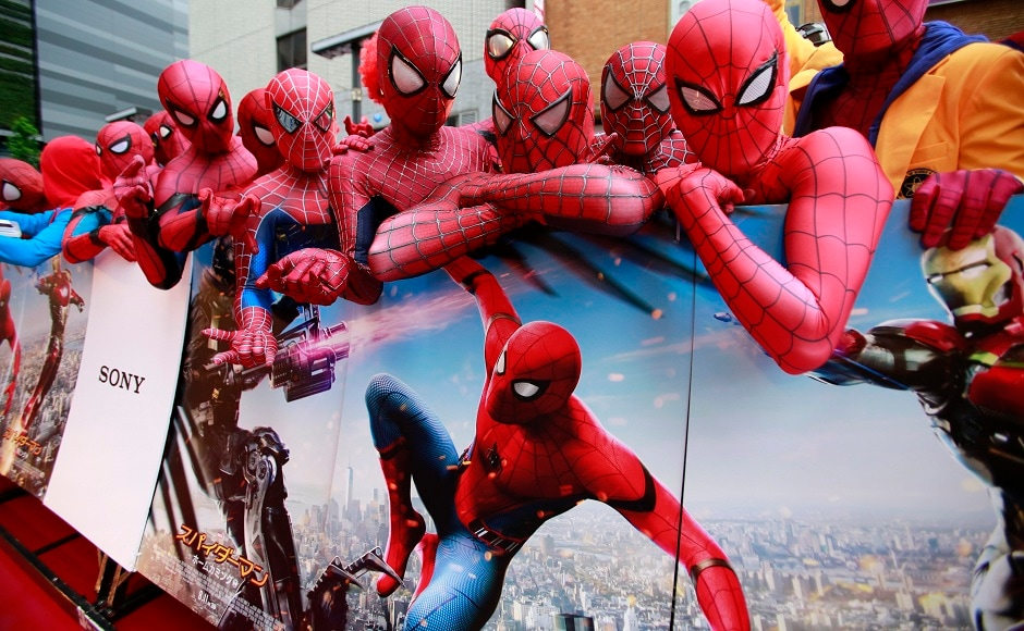 Spider-Man fans dressed as his costume pose with the movie's posters prior to the Japan premiere for the 'Spider-Man: Homecoming' in Tokyo, Monday, 7 August, 2017. Image via AP/Shizuo Kambayashi.