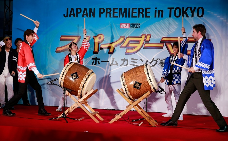 Holland (left) and director Jon Watts (right), beat traditional drums during the Japan premiere for their latest film 'Spider-Man: Homecoming' in Tokyo, Monday, 7 August, 2017. Image via AP/Shizuo Kambayashi.
