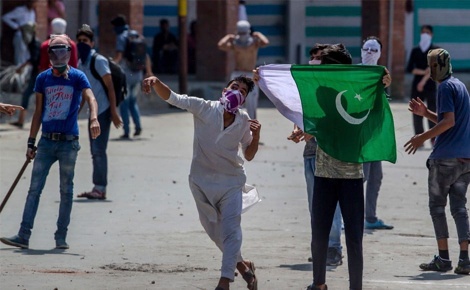 A Kashmiri protester throws a rock at government forces in Srinagar on Friday. In response, Mufti said Modi assured her to protect the Constitution's Article 35A which empowers the state legislature to declare permanent residents of the state and their privileges. AP