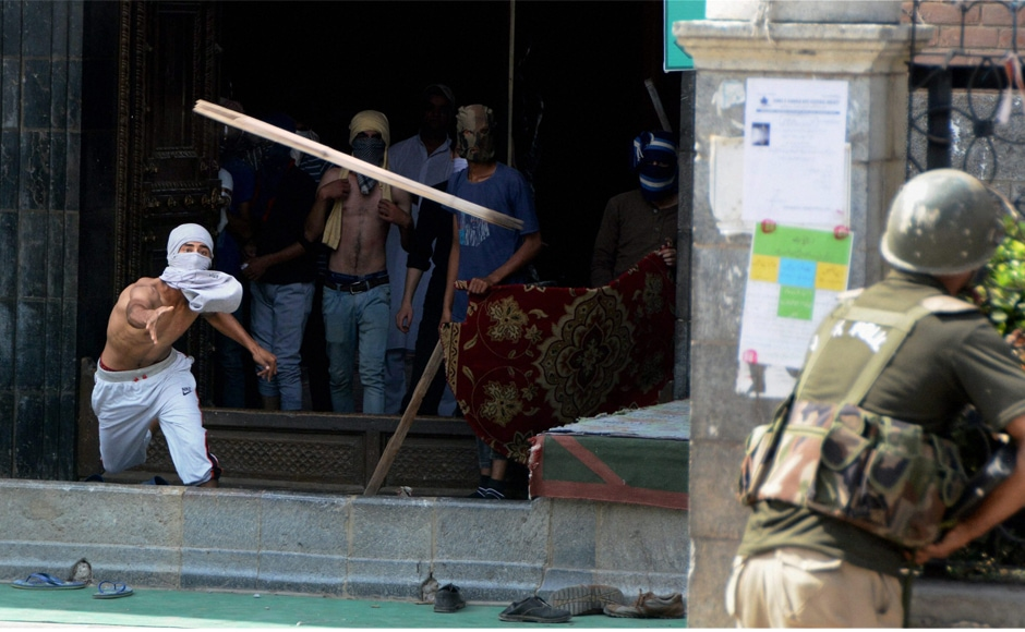 "A youth throws a wooden rod towards a policeman during clashes after the protests in Srinagar on Friday. Omar Abdullah, former chief minister, said what Mufti said did not matter and asked the Prime Minister's Office for clarifying the ""assurances"". PTI"