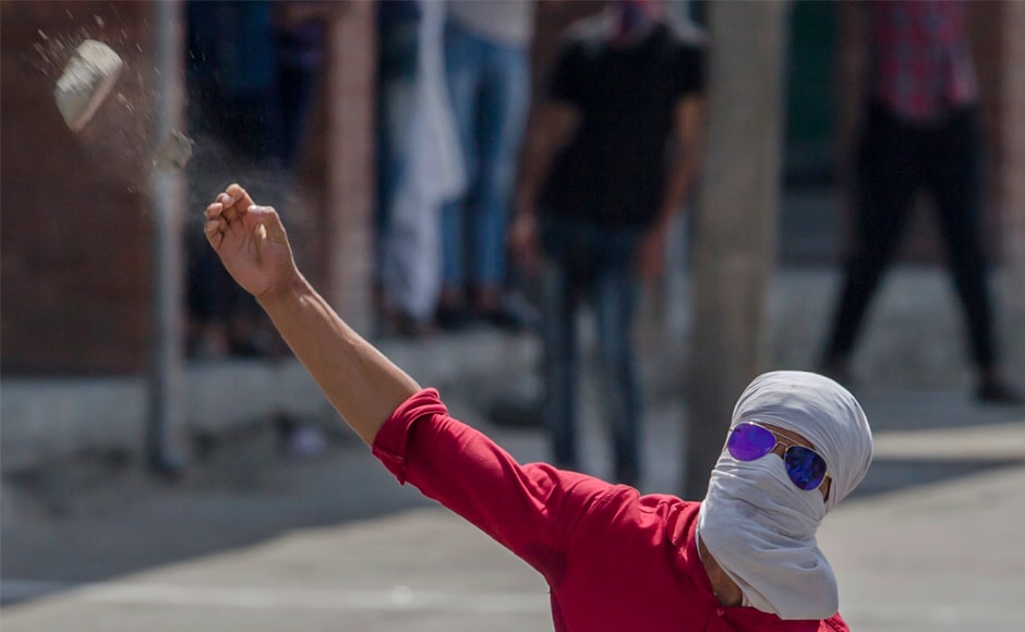 "A Kashmiri protester throws a rock at government forces in Srinagar. The BJP state unit on Thursday, however, had said that it was time to revoke Article 35A for it created a ""separatist emotion"" in the state. AP"