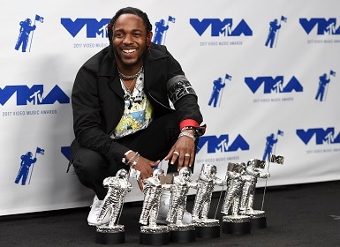 Kendrick Lamar poses in the press room with his awards. Image from AP.