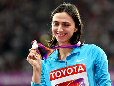 Russia's Maria Lasitskene holds her medal after defending her high jump title. AP