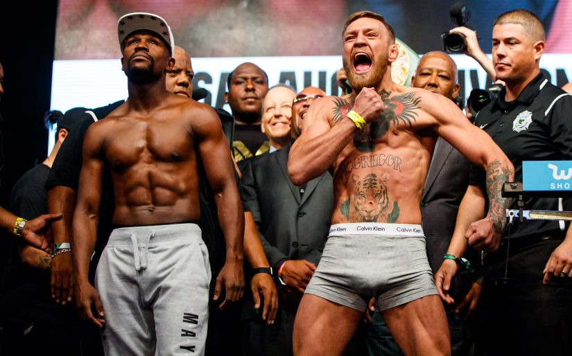 Conor McGregor (right) reacts alongside Floyd Mayweather during weigh ins for the upcoming boxing match at T-Mobile Arena. Reuters