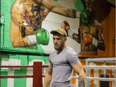 Conor McGregor poses in-front of mural of him punching Floyd Mayweather in his gym. Image Courtesy: Instagram @thenotoriousmma