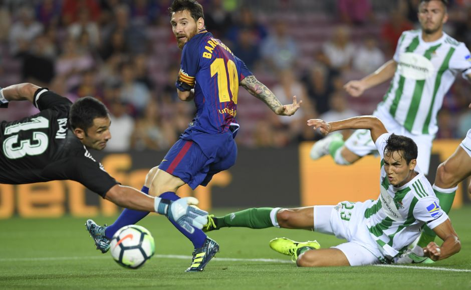 Barcelona's Lionel Messi looks on as Betis defender Alin Tosca diverts Gerard Deulofeu cross into his own net to give Barcelona the lead. AFP