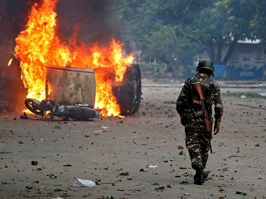 File image of a  member of the security forces walking toward a burning vehicles  during violence in Panchkula. Reuters