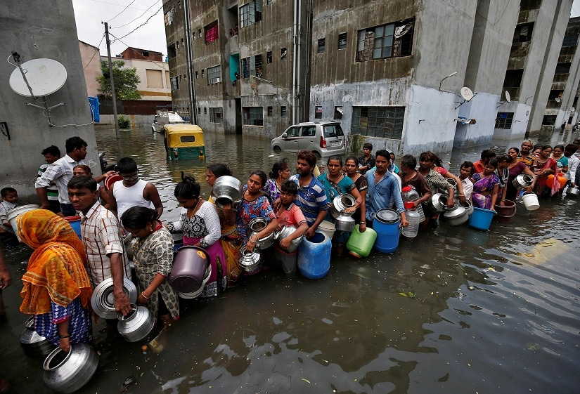 People queue to collect drinking water from a municipal tanker at a flooded residential colony in Ahmedabad, India, July 29, 2017. REUTERS/Amit Dave TPX IMAGES OF THE DAY - RTS19NNE
