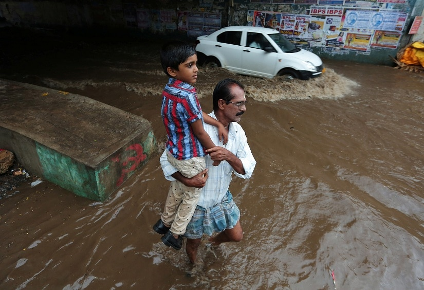 A man carries a child as he wades through a waterlogged subway after heavy rains in Chennai, India August 9, 2017. REUTERS/P.Ravikumar - RTS1B1WP