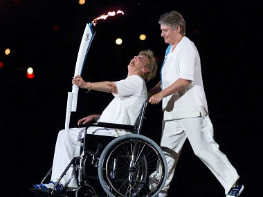 Former Australian multi-Olympic gold medallist sprinter Betty Cuthbert, who suffers from multiple schlerosis, carries the torch in a wheelchair pushed by former sprinter Raelene Boyle, during the opening ceremony of Sydney's Olympic Games September 15, 2000. Athletes from 199 nations are participating in the XXVII Summer Olympic Games which will continue until October 1. - RTXJZI9