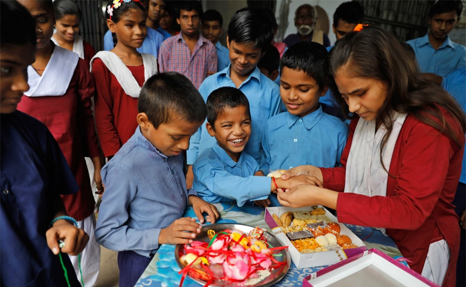A blind boy reacts as a girl ties a rakhi, a sacred thread, on his wrist, as other students look on at the State Blind School, Allahabad on the occasion of Raksha Bandhan. AP