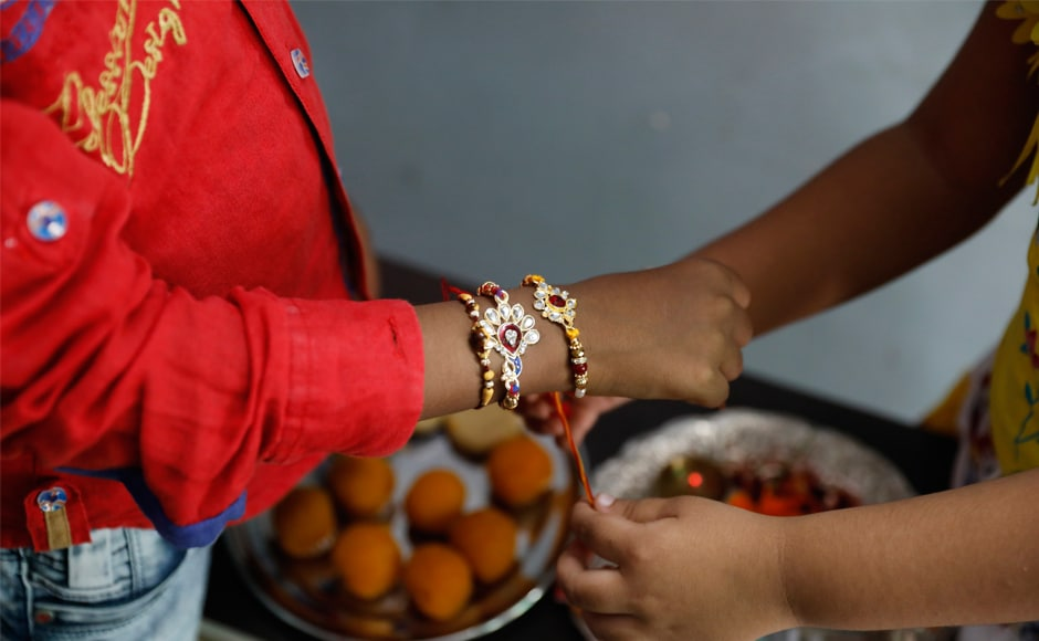 A girl ties rakhis on her brother's wrist in Allahabad. During the festival, sisters tie a sacred thread (rakhi) around their brothers wrists, and with the brothers vowing to protect their sisters. AP