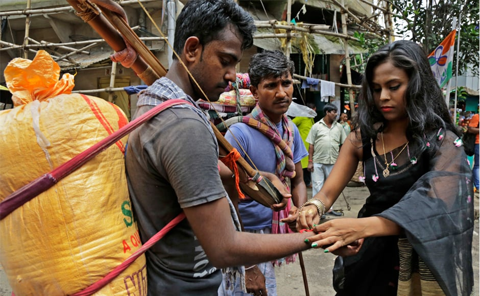 An Indian sex worker, right, ties a rakhi on the wrist of a commuter inside Sonagachhi, the biggest red light district in Kolkata. AP