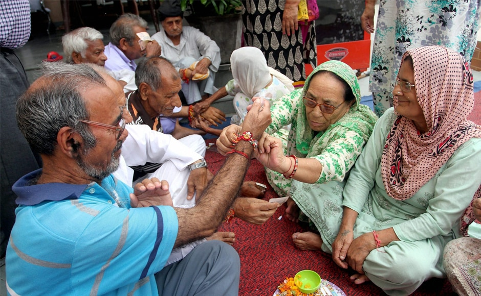 Women residing in an old age home tie rakhis to men on Raksha Bandhan, in Jammu on Monday. The festival is celebrated on the full moon day in the Hindu month of Shravana. PTI