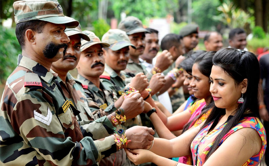 Women tie rakhis to Indian Army soldiers in Bhubaneswar on Monday. PTI