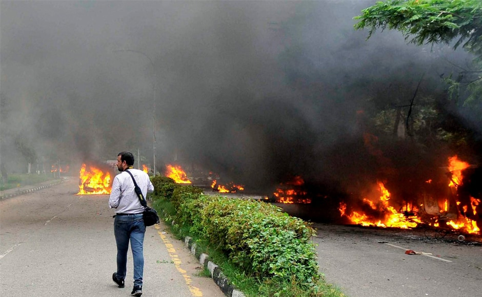A cameraperson walks towards vehicles burning following violence caused by Dera Sacha Sauda followers after Gurmeet Ram Rahim's conviction in Panchkula. Nearly 32 people lost their lives in the clashes, as per latest reports. PTI