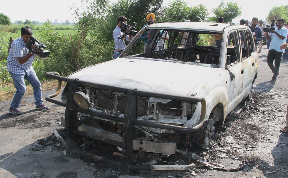 The burnt remains of a car torched by unknown people at Kotli village in Sirsa on Monday. Dera followers allegedly set two cars on fire near the DSS headquarters in Sirsa, before the sentence was pronounced. PTI