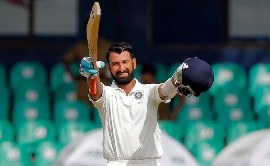 India's Cheteshwar Pujara raised his bat and helmet to celebrate his 13 Test century. It was also his 2nd century of the series and 3rd against the hosts Sri Lanka. Pujara remained unbeaten on 128. AP