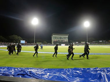 Sri Lankan police personnel run towards boundary to bring situation under control after some spectators threw plastic bottles in the ground to disrupt the play during the third one-day international cricket match between Sri Lanka and India in Pallekele, Sri Lanka, Sunday, Aug. 27, 2017. (AP Photo/Eranga Jayawardena)